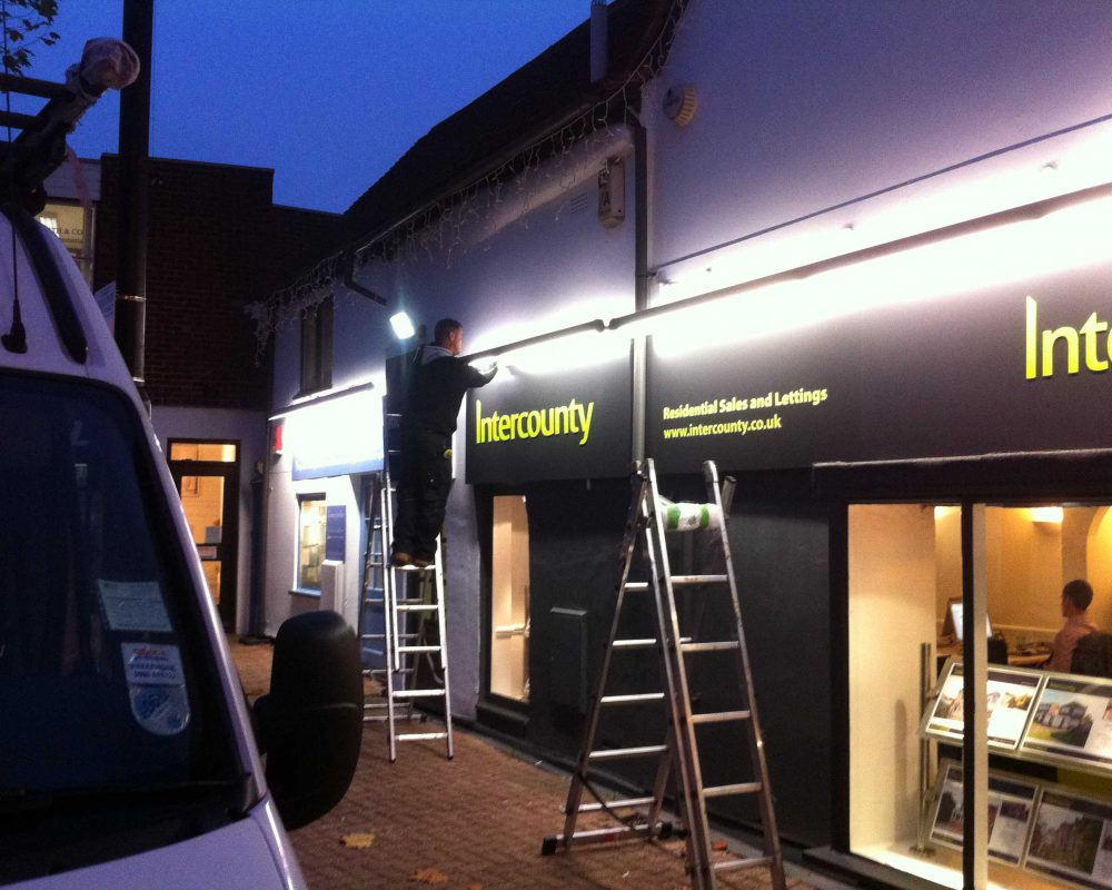 A team installing a new illuminated fascia.